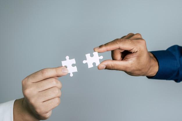 ビジネスマンパートナーがカップルのパズルのピースを接続して、成功を目標とするマッチングを一緒にしようとしています