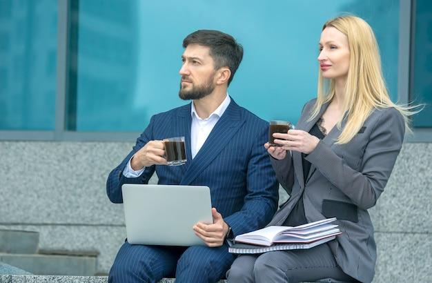 사업가들은 도시 거리에 있는 남녀가 사업 프로젝트에 대해 논의하고 커피를 마신다