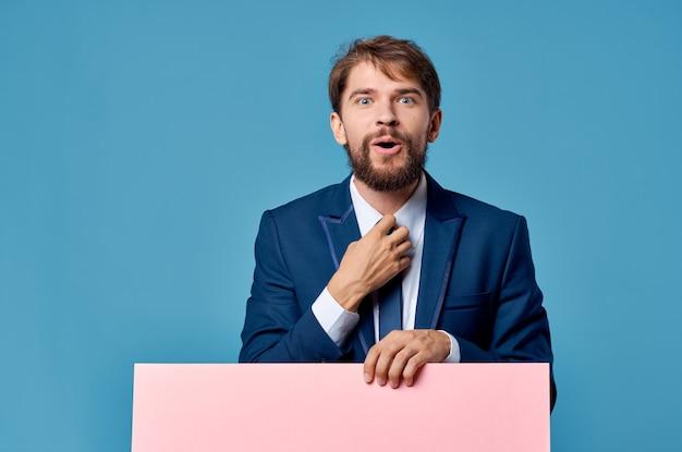 手青い背景のビジネスマンピンクのモックアップポスター。高品質の写真
