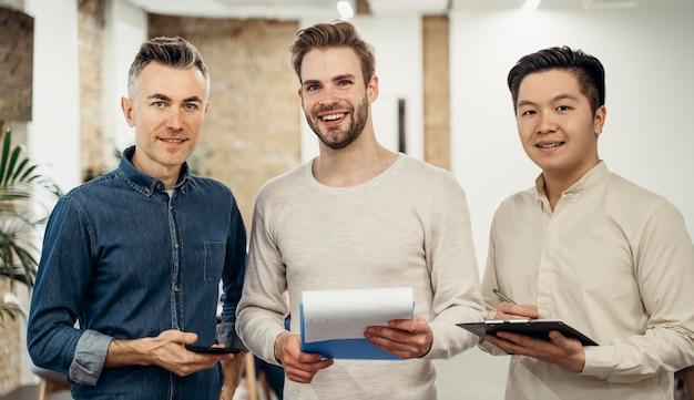 Бизнесмены вместе позируют в офисе