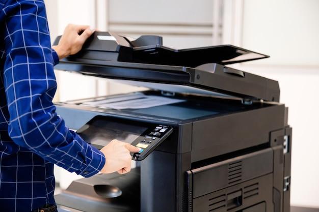 ビジネスマンは、オフィスでドキュメント用紙を印刷およびスキャンするためにコピー機またはプリンターを使用するために、パネルのボタンを押します。