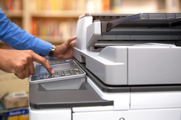 ビジネスマンはコピー機のパネルのボタンを押す