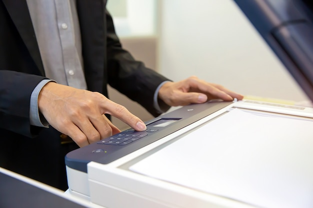Businessmen press button on the panel of photocopier.