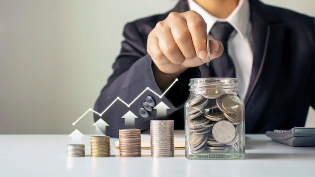 ビジネスマンは、経済成長のグラフ、お金を節約するアイデア、持続可能な投資などのコインを貯蓄ボトルに入れます。