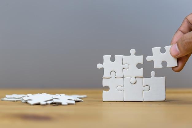 Businessmen put the last puzzle piece, business service concept to success.