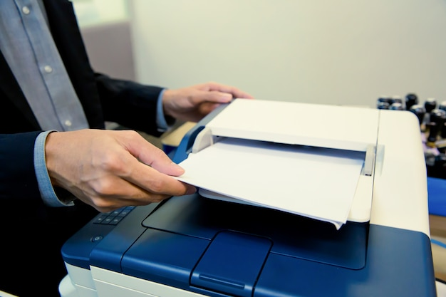 Businessmen put a paper to tray on photocopiers.
