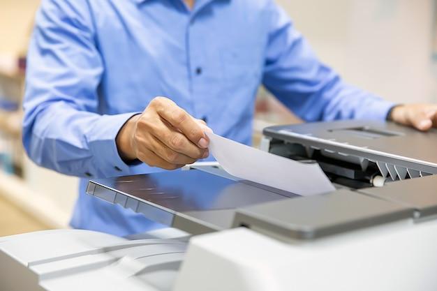 ビジネスマンは、オフィスの職場で書類をコピーしてスキャンするために、コピー機に書類を置きます。