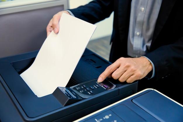 ビジネスマンは紙を入れて、コピー機のパネルのボタンを渡します。