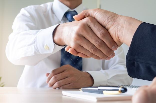 会社登記の契約書類を完成させた後、握手をするビジネスマン。契約と弁護士の会議のコンセプト
