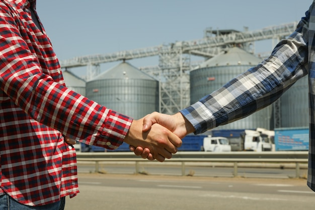 Businessmen shake hands against silos. agriculture business