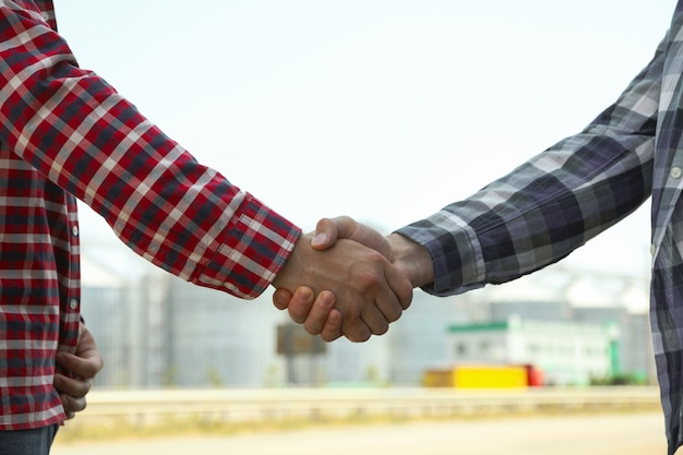 ビジネスマンはサイロに対して手を振る。農業事業