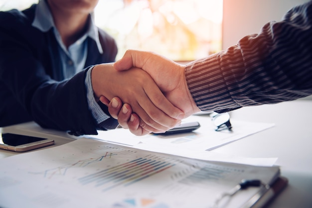 Businessmen shake hands with successful partners and congratulate