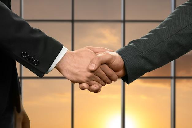 お互いの手を振るビジネスマン。マネージャー&#39;日当たりの良い背景で挨拶。明るい未来が私たちを待っています。信頼と信仰。