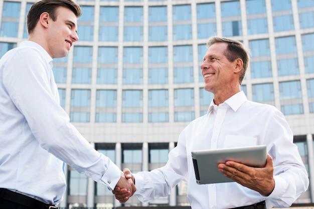 Businessmen shaking hands near building