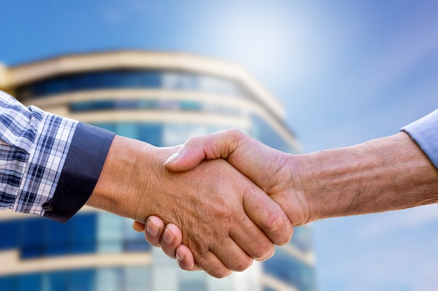 Businessmen shaking hands when buying a home. handshake of men on modern home
