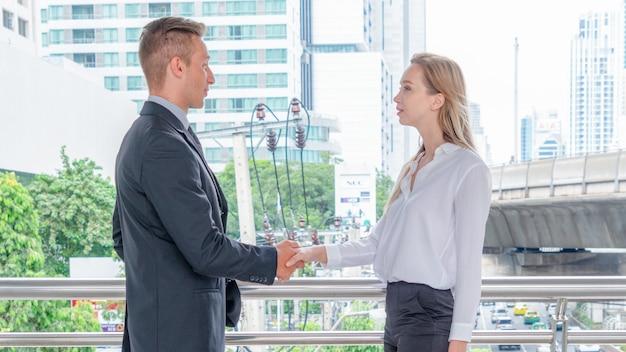 屋外空間で女性と握手するビジネスマン。