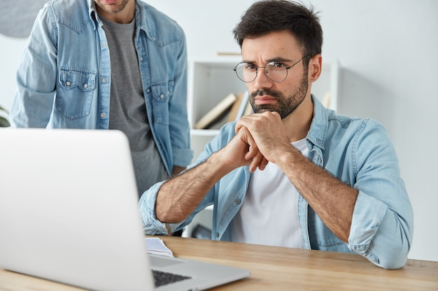 Businessmen sit at office desk together, work and communicate, concentrated into laptop computer