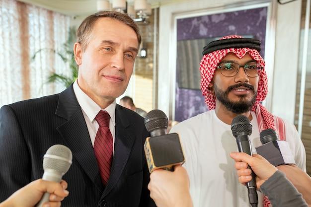 インタビュー中にマイクを持ってジャーナリストの前に立っているビジネスマン