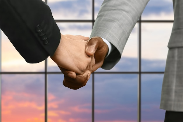 Businessmen in suits shake hands. handshake of leaders at sunset. always act natural. international trade agreement.