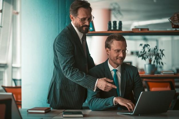 Работа в команде бизнесменов с ноутбуком. два кавказских человека, планирующие стратегию развития проекта на компьютере в современном офисе.