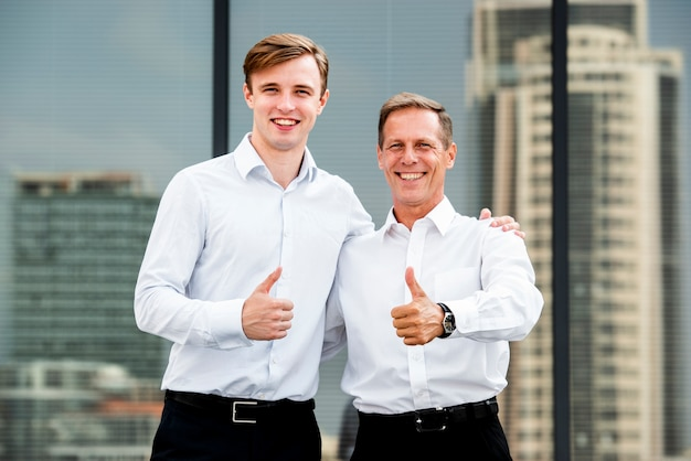 Businessmen thumbs up gesture near building
