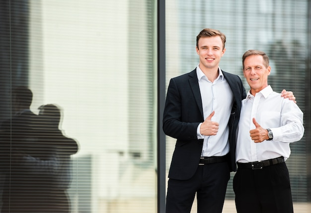 Businessmen thumbs up looking at camera