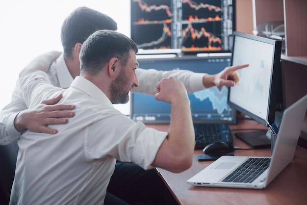 온라인 주식을 거래하는 기업인. 여러 컴퓨터 화면에서 그래프, 인덱스 및 숫자를보고있는 주식 중개인. 상인 사무실에서 논의중인 동료. 비즈니스 성공 개념입니다.