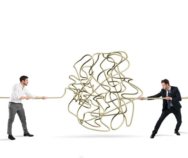ビジネスマンはもつれたロープを解決しようとします。パートナーシップと協力の概念