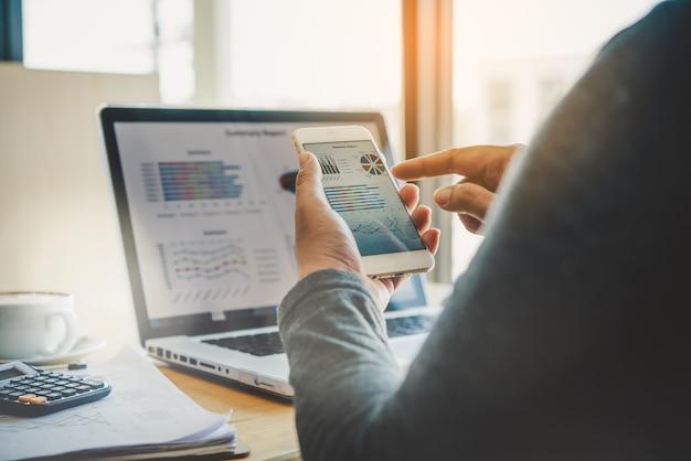 ビジネスマンはスマートフォンとラップトップを使用して接続し、オフィスで情報を検索します