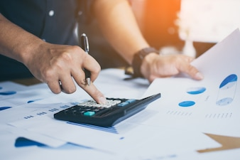 Businessmen use the calculator to calculate and analyze the company's profits