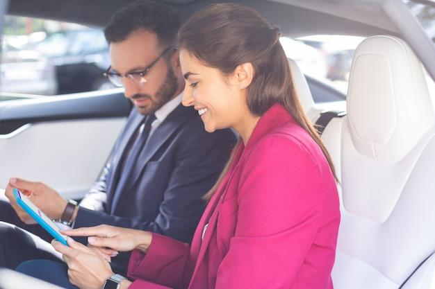 태블릿을 사용하는 기업인. 고양이에 앉아있는 동안 태블릿을 사용하는 성공적인 젊은 사업가의 커플