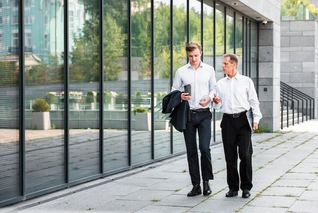Businessmen walking near building