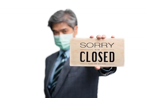 ビジネスマンは孤立した背景に医療マスクを着用し、申し訳ありませんが閉じたサインを保持しています