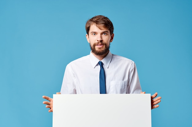 青い背景を宣伝する手でビジネスマンの白いモックアップポスター