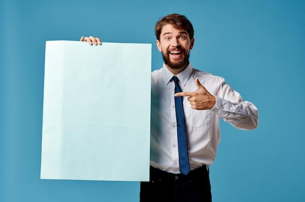 青いモックアップポスターサインコピースペース孤立した背景を持つビジネスマン。高品質の写真