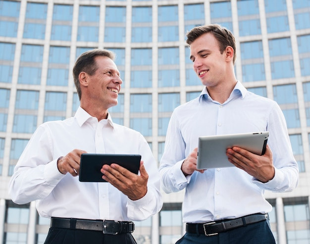 Businessmen with tablets looking at each other