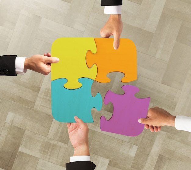 Businessmen working together to build a colored puzzle