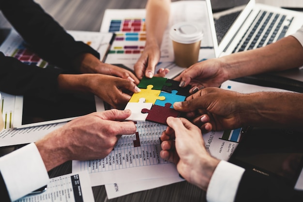 Бизнесмены работают вместе, чтобы собрать цветной пазл