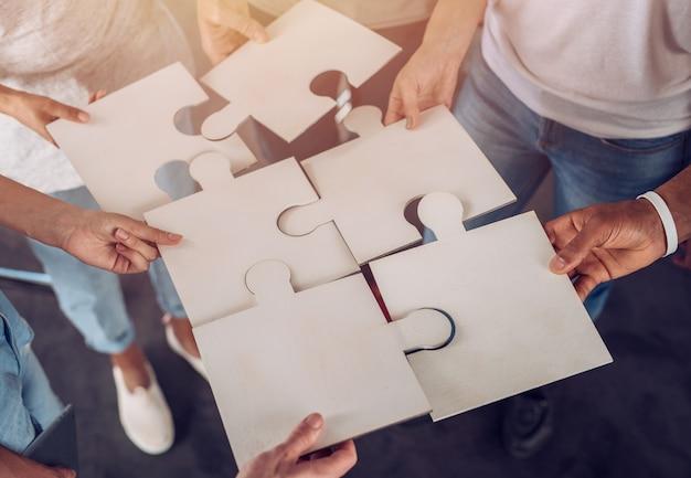 パズルを構築するために一緒に働くビジネスマン。チームワーク、パートナーシップ、統合、スタートアップの概念。