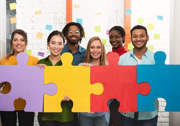 퍼즐을 구축하기 위해 협력하는 기업인. 팀워크, 파트너십, 통합 및 시작의 개념.