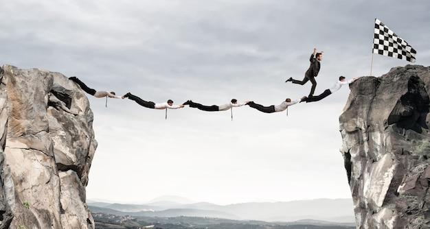 Бизнесмены вместе создают мост между двумя горами, чтобы добраться до флага. концепция бизнес-цели достижения