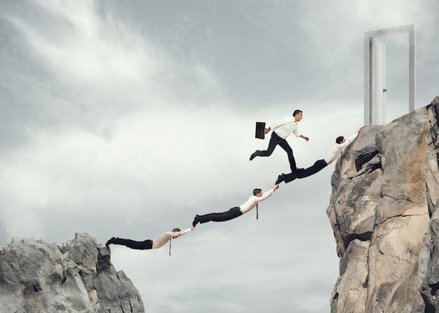 Бизнесмены вместе создают мост между двумя горами, чтобы добраться до двери. понятие амбиций в бизнесе