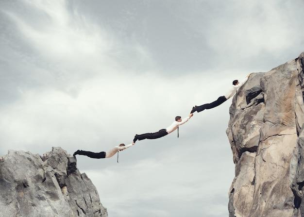 Бизнесмены вместе создают мост между двумя горами