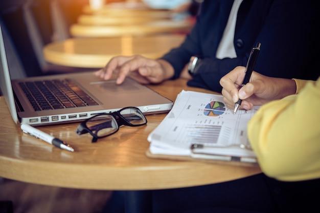 Бизнесмены работая с компьтер-книжкой и smartphone в офисе открытого пространства. отчет о встрече в процессе