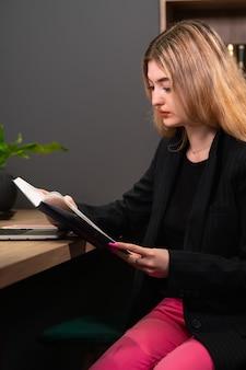 Деловой человек сидит и читает книгу или журнал за своим столом в офисе, пока она изучает свою повестку дня или проводит исследование рынка, крупным планом, кадрированным изображением.