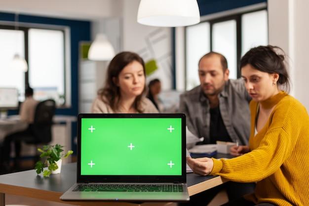 Бизнесмены, анализирующие годовые финансовые отчеты, сидя за столом в задней части ноутбука с зеленым экраном с цветными клавишами, макет рабочего стола