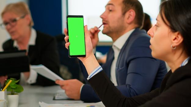 기업인들은 직원이 녹색 화면 모니터로 전화를 들고 있는 동안 책상에 앉아 연간 재무 보고서를 분석합니다. 크로마 키 디스플레이가 있는 그린스크린 pc를 사용하여 프로젝트 전략을 설명하는 리더