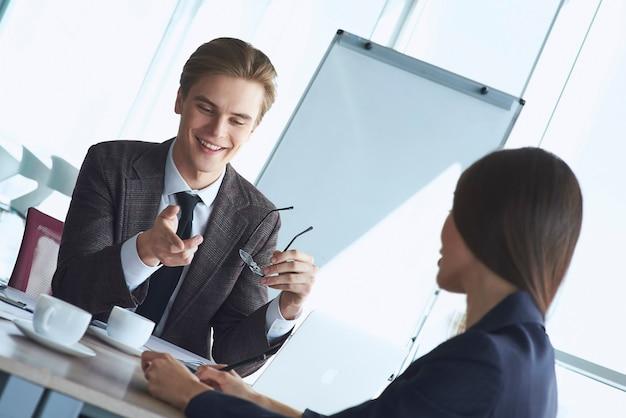 Бизнесмены в офисе, работая вместе, сидя обсуждают мошенничество