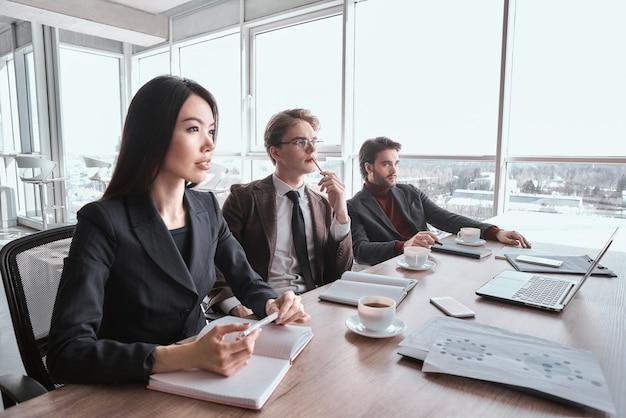 Бизнесмены в офисе, работая вместе, сидя на конференции