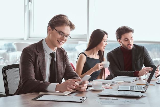 Бизнесмены в офисе, работая вместе, сидя в очках